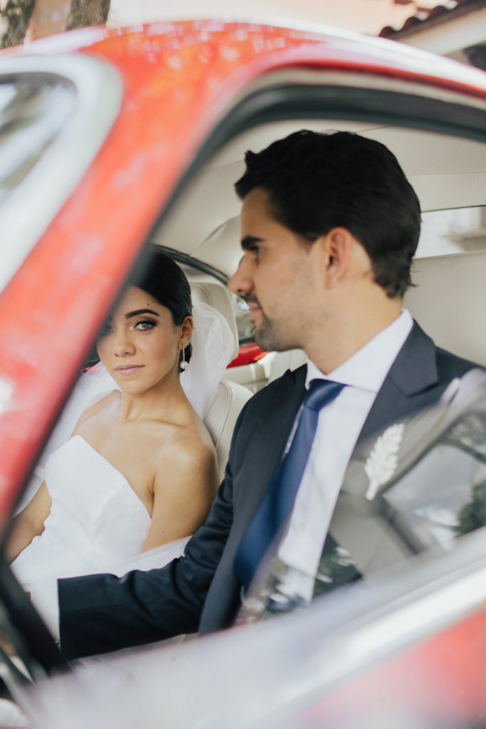 This image portrays the couple of the wedding wedding ceremony in Guadalajara, Mexico, inside a red car through the window.
